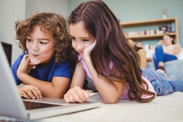 Close-up de irmãos olhando no laptop em casa