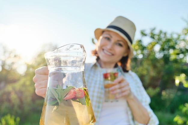 Close-up de jarro e copo com bebida natural de morango e hortelã nas mãos de uma mulher