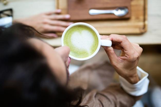 Close-up de jovem bebendo chá verde matcha com leite na mesa de madeira na cafeteria. vista do topo.