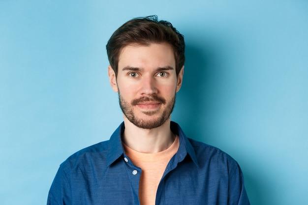 Close-up de jovem caucasiano com barba, sorrindo e olhando feliz para a câmera, de pé sobre fundo azul.