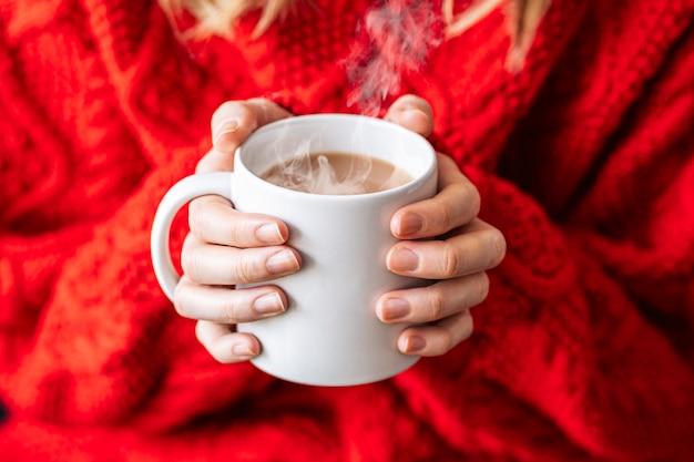Close-up de jovem com blusa de algodão vermelho, segurando uma caneca de café quente. inverno.