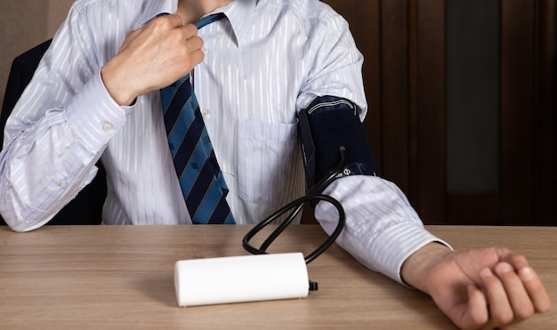 Close-up de jovem em uma camisa e gravata, medindo sua pressão arterial.