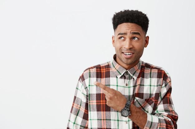 Close-up de jovem estudante masculino americano de pele escura bonito com penteado encaracolado em camisa quadriculada de manga comprida, apontando de lado com o dedo indicador na parede branca com expressão de rosto cínico