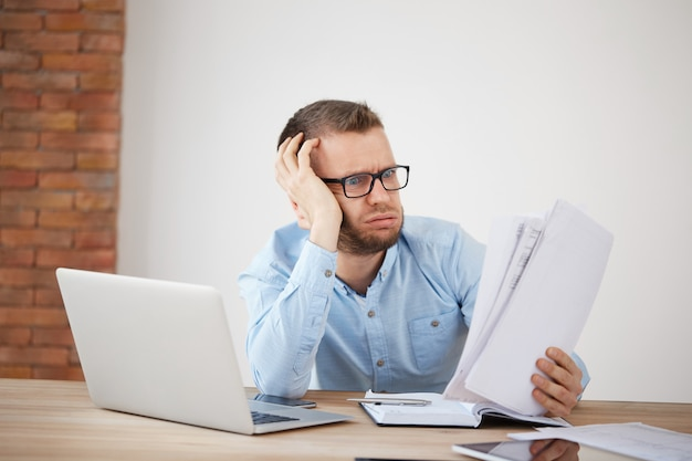 Close-up de jovem gerente de finanças masculino barbudo infeliz exausto sentado no escritório no final da noite