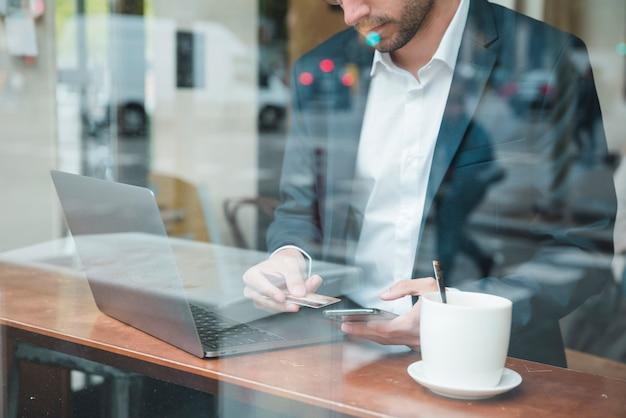 Close-up, de, jovem, homem negócios, usando, cartão crédito, ligado, telefone móvel, em, café