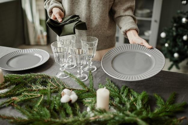Close-up de jovem montando pratos na mesa de jantar decorada para o natal com galhos de pinheiro.
