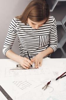 Close-up de jovem profissional bonita morena magro de camisa listrada, trabalhando na nova planta para o projeto de equipe futura
