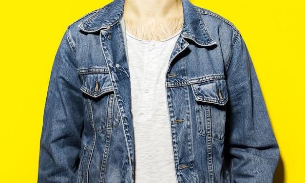 Close-up de jovem, vestindo jaqueta jeans e camisa branca sobre fundo amarelo.