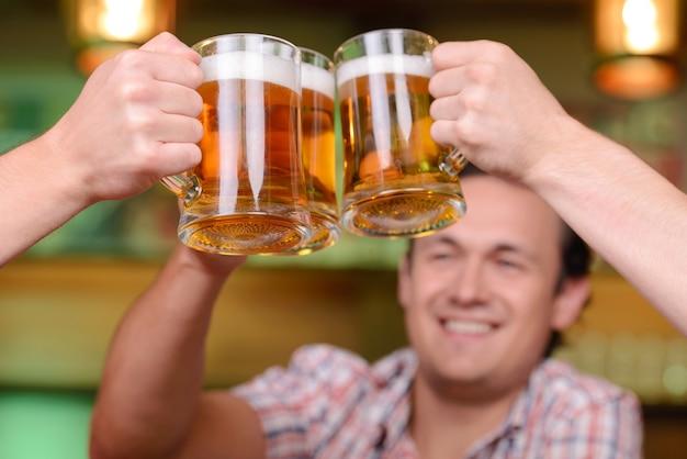 Close-up de jovens gays para segurar copos de cerveja.