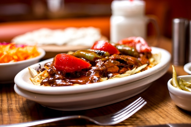 Close-up de kebab de carne turca, guarnecido com molho de tomate picante