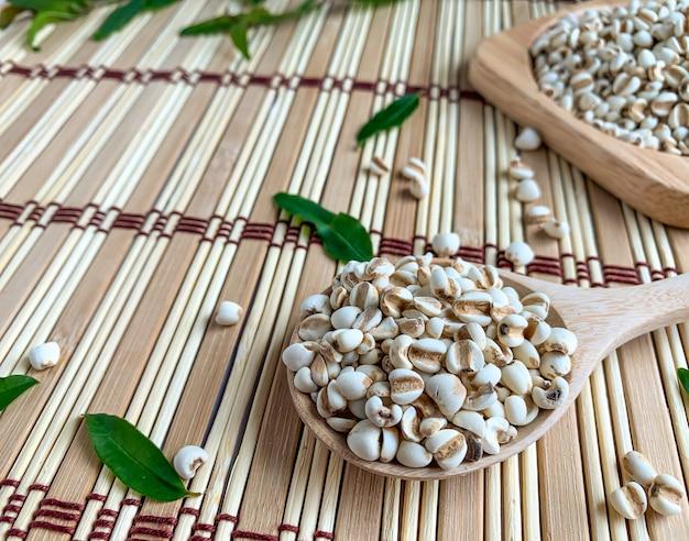 Close up de lágrimas ou painço de trabalho em uma bandeja e uma colher de pau. o fundo é um tapete de madeira decorado com folhas de romã