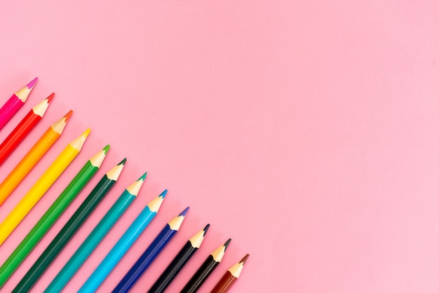 Close-up de lápis de cor com cor diferente sobre fundo rosa com copyspace