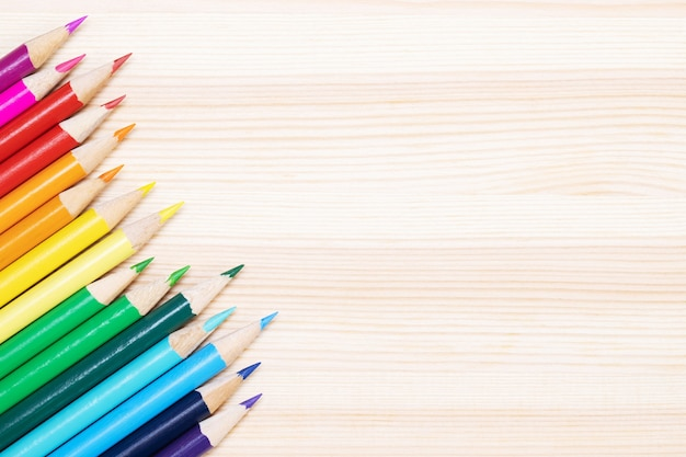 Close up de lápis de cor com pontas com pontas de lápis alinhadas na mesa de madeira