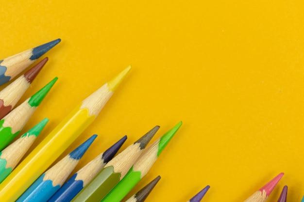 Close-up de lápis de cor nítidos em um background amarelo de mesa, espaço de cópia, foto de vista superior
