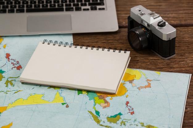 Close-up de laptop, câmera, bloco de notas e mapas