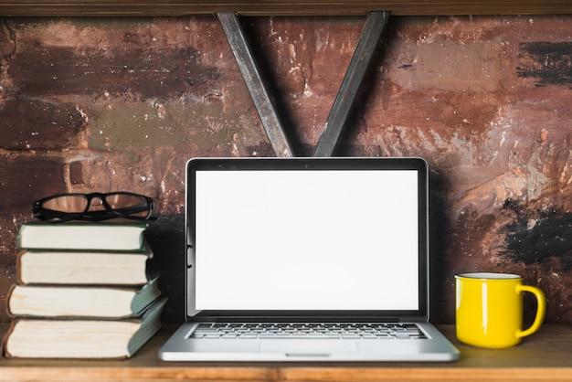 Close-up de laptop; livros empilhados; óculos e copo na prateleira de madeira