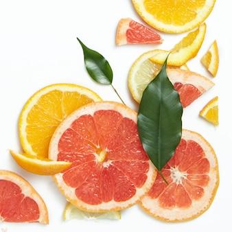 Close up de laranja fresca, toranja, limão e rodelas de limão na superfície branca