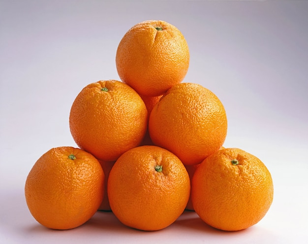 Close up de laranjas em cima da outra em uma superfície branca - ótimo para um plano de fundo