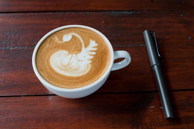 Close-up de latte art café em copo branco com caneta
