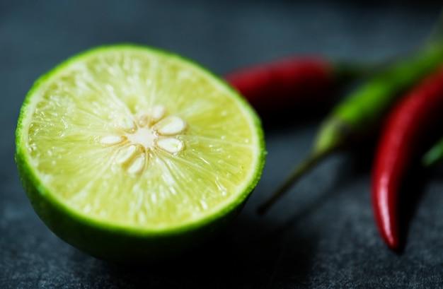 Close-up de limão cortado e pimenta no fundo preto