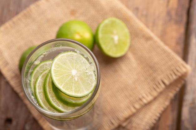 Close-up de limão fatiado no copo com água com gás e metade do limão verde no saco de tecido e mesa de madeira