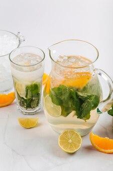 Close-up de limonada de laranja e limão em uma jarra e vidro isolado