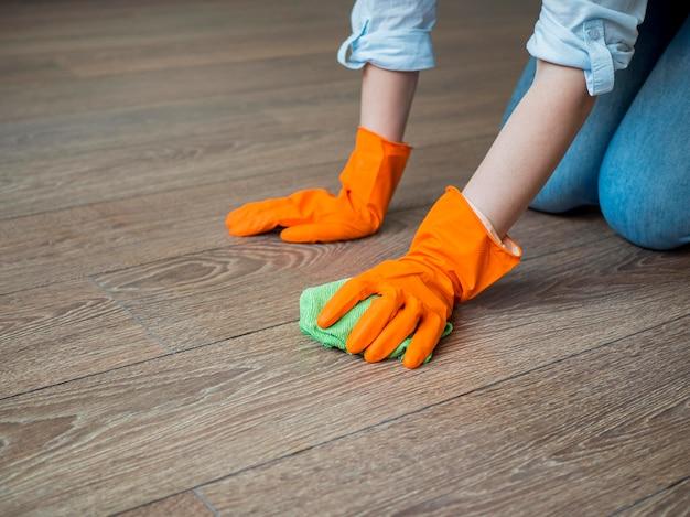 Close-up de limpeza do chão com luvas de borracha