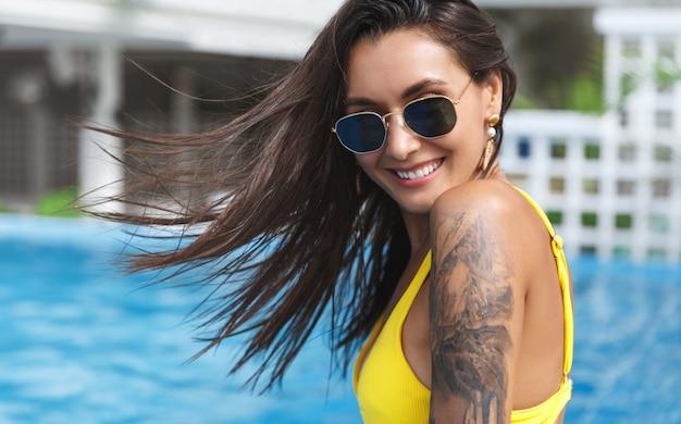 Close-up de linda mulher bronzeada com tatuagem em biquíni amarelo, sorrindo, câmera perto da piscina.