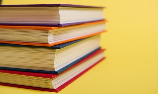 Close-up de livros multicoloridos empilhados sobre fundo de superfície amarelo, com espaço de cópia para o texto. conceito do dia do professor, conhecimento, literatura, leitura, erudição