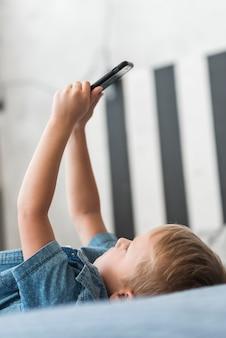 Close-up, de, loiro, menino, encontrar-se cama, usando, telefone móvel