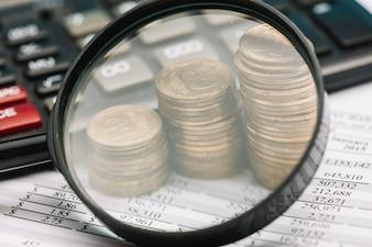 Close-up, de, lupa, sobre, a, pilha, moedas, e, calculadora, ligado, balancete financeiro