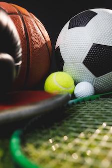 Close-up de luvas de boxe e bolas de golfe e tênis de futebol de basquete