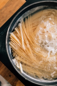 Close-up de macarrão espaguete em ebulição de água quente em panela de aço.