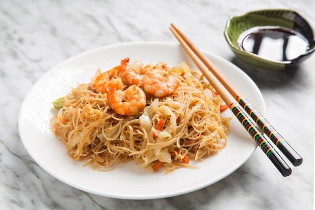 Close up de macarronetes chineses com camarão e vegetais.