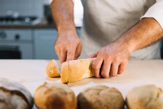 Close-up, de, macho, baker's, mão, corte, pão, com, faca, ligado, contador cozinha