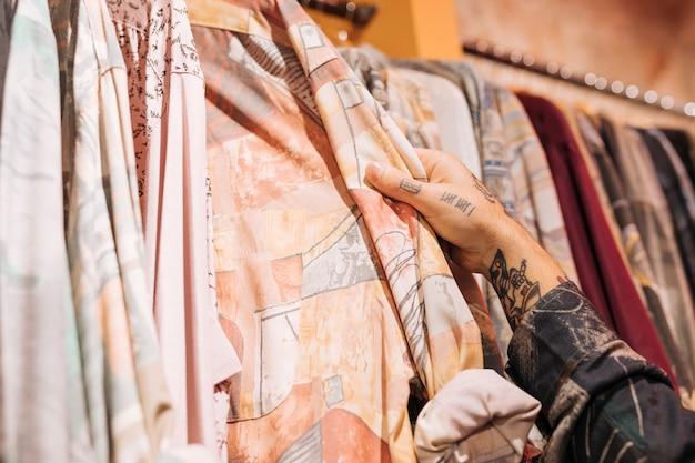 Close-up, de, macho, customer's, mão, escolher, a, camisa, pendurar, a, trilho, em, a, loja