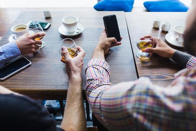 Close-up, de, machos, passe segurar, copos bebidas, usando, telefone móvel