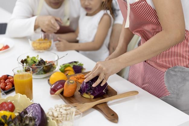 Close-up de mãe cortar legumes na cozinha