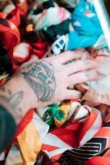 Close-up, de, male's, mão, com, tatuagem, tocar, echarpe, em, loja