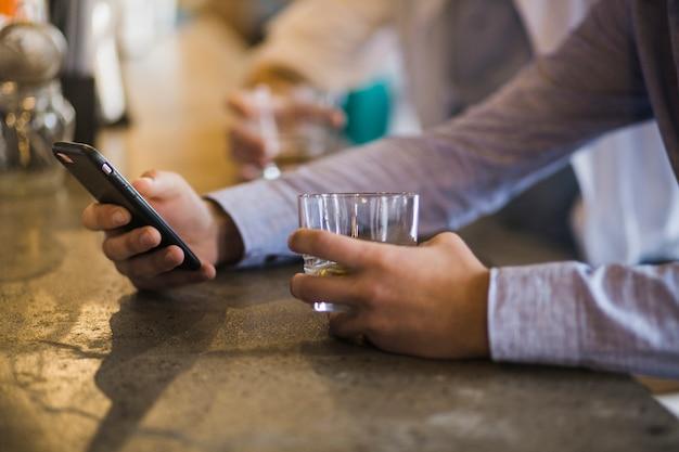 Close-up, de, male's, mão, copo segurando, de, bebidas, usando, telefone móvel