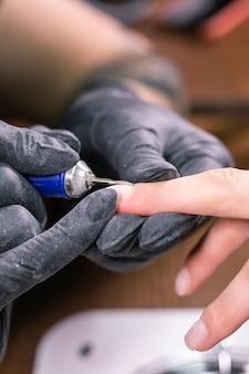 Close-up de manicure do processo. preparação para manicure de ferragens. esteticista em luvas de borracha corta o