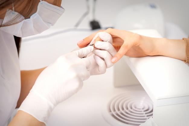 Close up de manicure master com manicure pinça corta cutículas de unhas femininas em salão de beleza