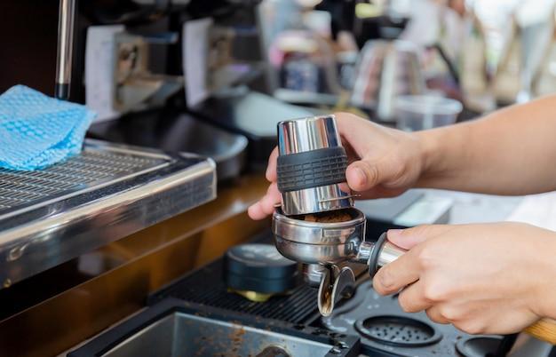 Close-up de mão barista fazendo café na máquina