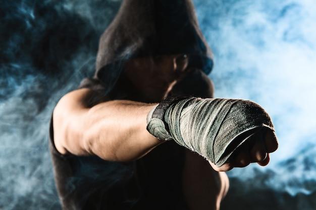 Close-up de mão com bandagem de homem musculoso treinando kickboxing na fumaça preta e azul