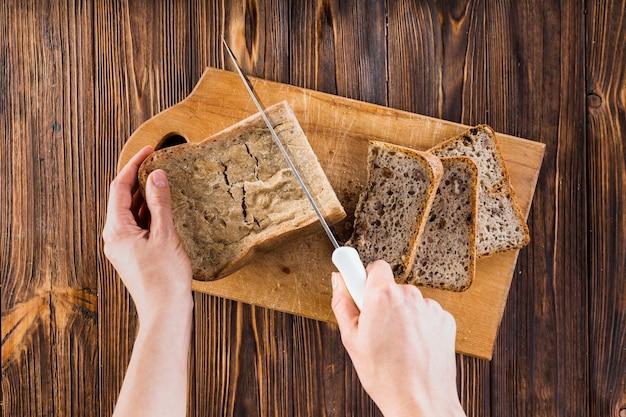Close-up, de, mão, corte, a, pão, com, faca, ligado, tábua cortante