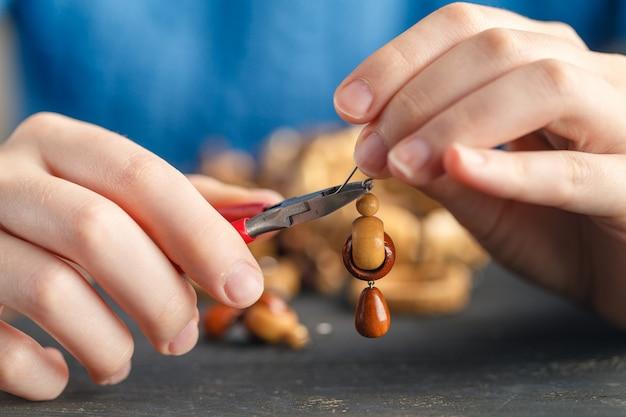 Close-up de mão de mulher enfiando contas no cordão para fazer colar ou pulseira artística do grânulo