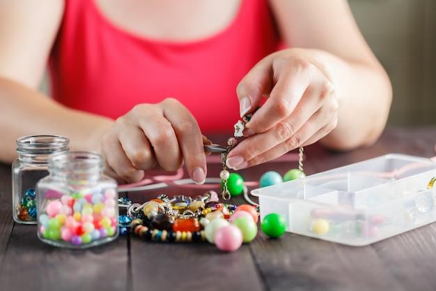 Close-up de mão de mulher enfiando contas
