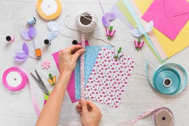 Close-up, de, mão, fita decorando, ligado, scrapbooking, cartão, ligado, textured, fundo