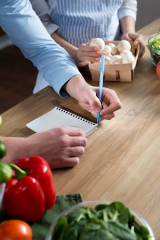 Close-up, de, mão homem, escrita, receita, em, diário, ligado, madeira, contador cozinha