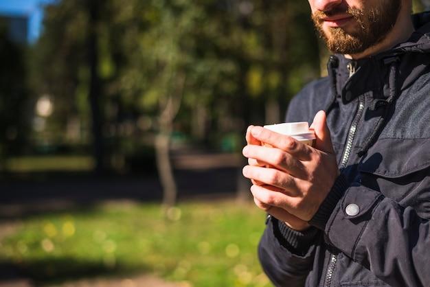 Close-up, de, mão homem, segurando, copo café descartável, em, a, jardim